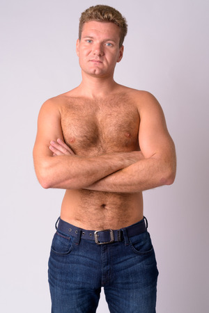 Foto de Portrait of young blonde shirtless man with chest hair crossing arms - Imagen libre de derechos