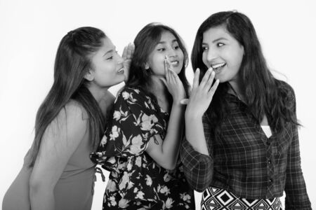 Photo for Studio shot of young happy Persian woman looking shocked with both friends whispering on one side - Royalty Free Image