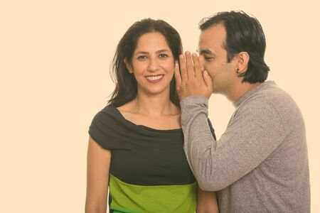 Photo for Happy Persian couple smiling while man whispering to woman - Royalty Free Image
