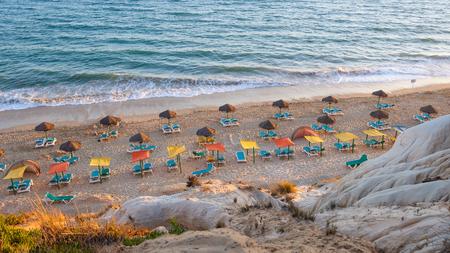 Foto de Sunbeds and umbrellas on the Falesia Beach in afternoon sun, Algarve, Portugal - Imagen libre de derechos