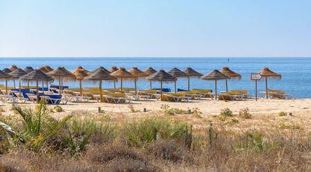 Foto de Straw umbrellas and sunbeds on the beach in Vilamoura, Algarve Portugal - Imagen libre de derechos