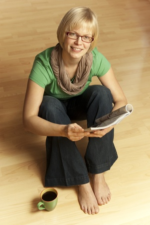young blonde woman sitting barefoot on the floor reading a magazine