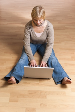 young woman with computer sitting barefoot on the floor, view from above