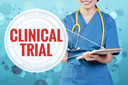 Foto de Smile female doctor with blurry blue glitter point to text: Clinical Trial - Imagen libre de derechos