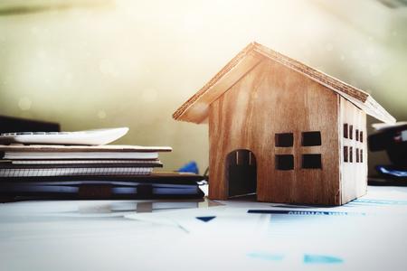 Foto de House and property for sale concept, wood house toy on office desk. - Imagen libre de derechos