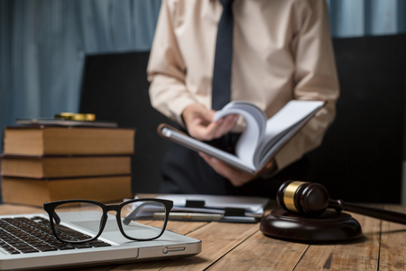 Photo for Business lawyer working hard at office desk workplace with book and documents. - Royalty Free Image