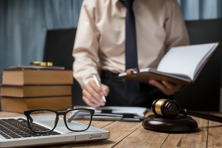 Foto de Business lawyer working hard at office desk workplace with book and documents. - Imagen libre de derechos