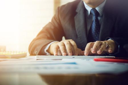 Foto de Asian business man using calculator to calculate the daily profit of a private business. - Imagen libre de derechos