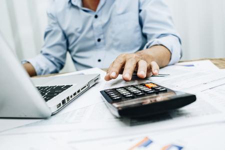 Foto de Business man accountant using calculator to calculating bugget money tax loan. - Imagen libre de derechos