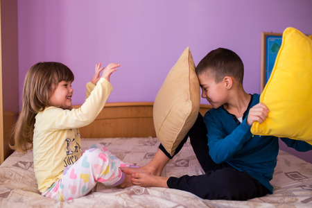 Photo pour Brother and sister having fun in a pillow fight. Little boy is holding a pillow, while the girl  hits him with her pillow. Both are wearing their pajamas  Happy children in a pillow fight - image libre de droit