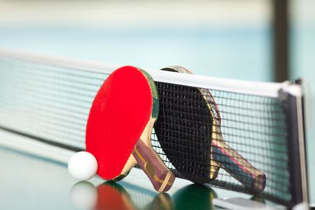 Two table tennis or rackets and balls on a green table with net