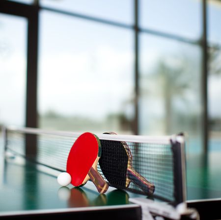 Two table tennis rackets and ball on a green table with net