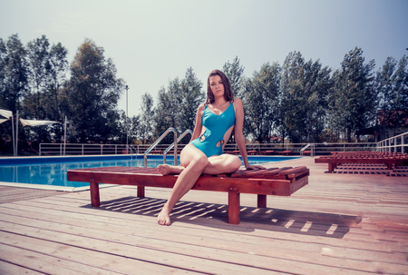 Foto de one young adult woman Caucasian model posing, sitting sunlounger, outdoors, hot sunny day, swimming pool, trees, one piece swimsuit. - Imagen libre de derechos