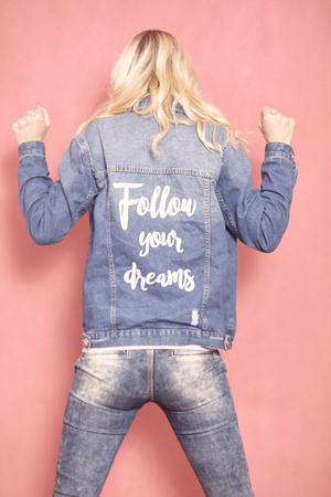 Foto de one young woman, 20-29 years old, long blond hair. Shot in studio on pink background. Wearing jeans jacket with sign follow your dreams on her back, (rear view). - Imagen libre de derechos
