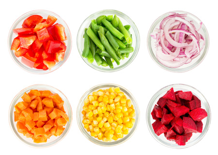 Foto de Assortment of cut vegetables in glass bowls isolated on white background. Top view. - Imagen libre de derechos