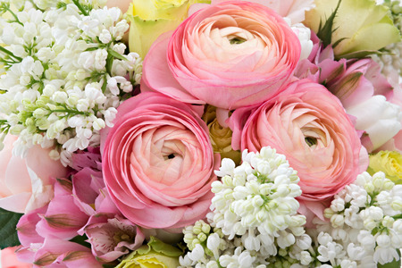 Photo pour Spring flowers background with pink buttercups, yellow roses, white lilac and alstroemeria - image libre de droit