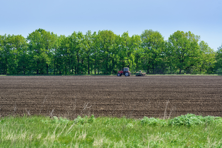 Photo pour Rural landscape with tractor plowing in the field - image libre de droit