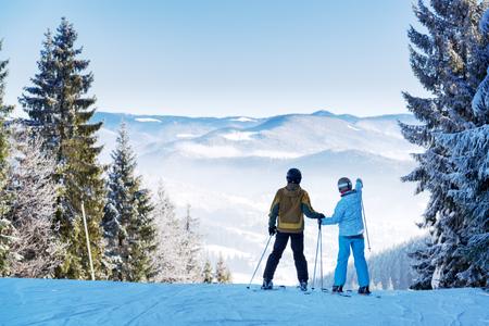 Photo pour Couple of skiers watching beautiful landscape of a winter resort - image libre de droit