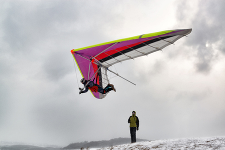 Photo for Kyiv, Ukraine. Pilot fly with a hang glider. Dramatic shot with strong wind and snow. - Royalty Free Image