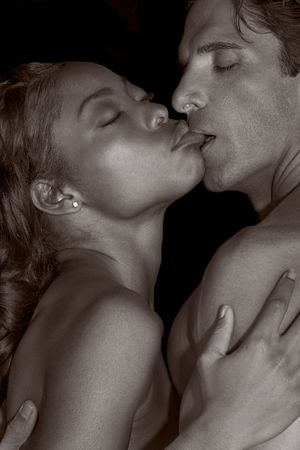 Loving affectionate nude interracial heterosexual couple in affectionate sensual kiss. Mid adult Caucasian men in late 30s and young black African-American woman in 20s