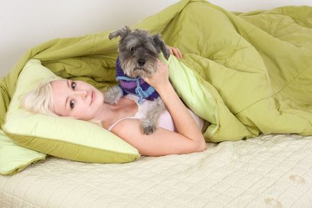 Caucasian blond young woman lying down on bed and holding dog of Schnauzer breed