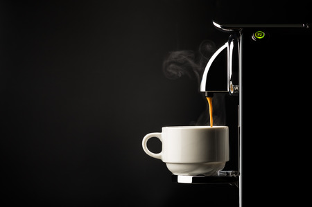 Photo pour Preparing a cup of strong freshly brewed espresso coffee using a coffee machine with a side view of the beverage pouring into a white cup on a dark shadowy background - image libre de droit
