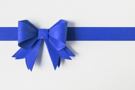 Blue ribbon on white recycled paper. Paper craft .