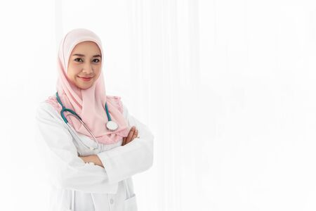 Foto per a beautiful young Islamic doctor woman with headphones stood across her arms and smiled confidently in the examination room near the window with curtains and white light from outside. Portrait photo. - Immagine Royalty Free