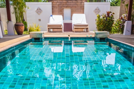 Photo for Swimming pool with clear blue water and two recliners - Royalty Free Image