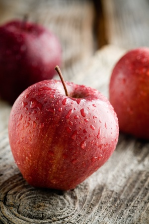 Photo for Three red apples on wooden table, selective focus - Royalty Free Image