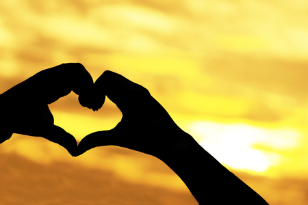 Silhouette hand with Heart shape gesture on sunset background