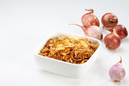 Fried onion in white bowl and onion isolated on white background