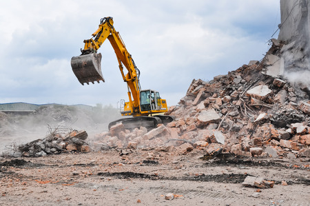 Photo for Excavator working at the demolition of an old industrial building. - Royalty Free Image