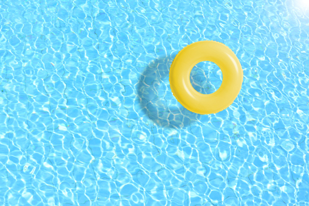 Photo pour yellow swimming pool ring float in blue water. concept color summer. - image libre de droit