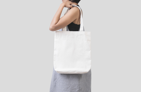 Photo for Girl is holding bag canvas fabric for mockup blank template isolated on gray background.  - Royalty Free Image