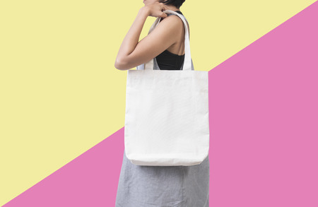 Photo pour Girl is holding bag canvas fabric for mockup blank template isolated on color background.  - image libre de droit