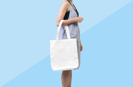 Foto de Girl is holding bag canvas fabric for mockup blank template isolated on blue background.  - Imagen libre de derechos