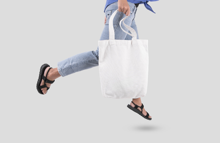 Photo pour Girl is holding bag canvas fabric for mockup blank template isolated on gray background.  - image libre de droit