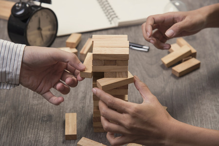 Photo pour Hand of engineer point a blocks wood tower game. concept prevent and solution. - image libre de droit