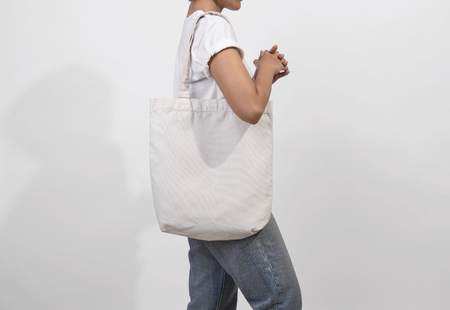 Foto de Girl is holding bag canvas fabric for mockup blank template isolated on gray background. - Imagen libre de derechos