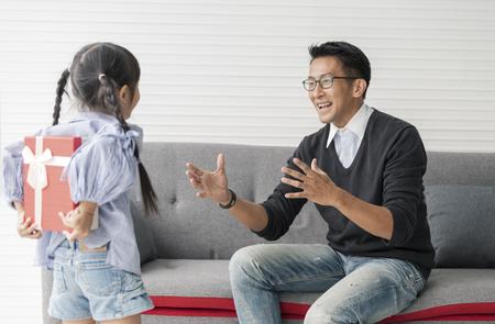Foto de Asian daughter give present for father. concept surprise for father's day. - Imagen libre de derechos