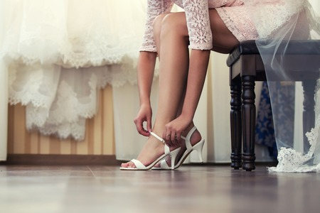Photo for Bride puts his shoes in the morning in the interior - Royalty Free Image