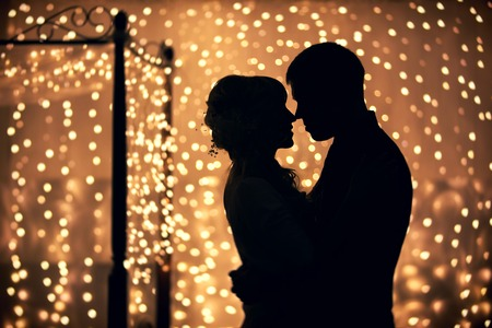 Foto de hugs lovers in silhouette against the background of garlands of lights - Imagen libre de derechos