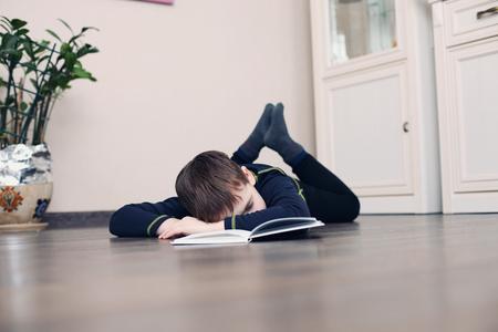 Foto de Image of young boy sleeping near books in the living room - Imagen libre de derechos