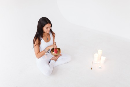 Photo pour girl the yogi plays on the Tibetan singing bowl. Yoga and healthy lifestyle concept. Girl the yogi wearing sportswear white suit, full length, white studio - image libre de droit