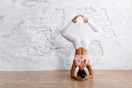 Foto de Unidentified beautiful young woman makes stand on her head with legs apart - an exercise of yoga - in an empty gym on white wall background - Imagen libre de derechos