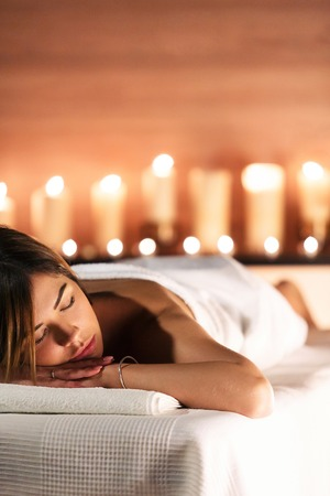 Photo for Spa concept. Beautiful young woman lies on massage table and relax on background of blurry candles. Beauty, spa, healthy lifestyle - Royalty Free Image