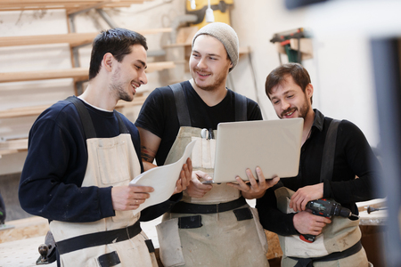 Photo for Master of small business with laptop and his team as sign of innovation in carpenter workshop. startup business, young specialist - Royalty Free Image