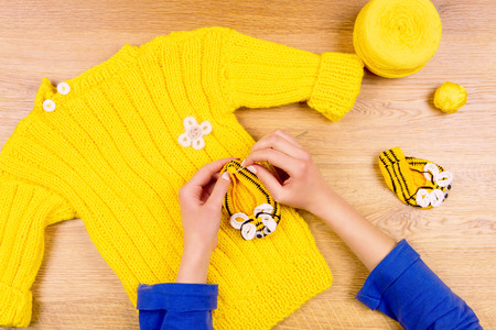 Foto für Dressmaker workplace. Woman female hands making yellow baby's bootees and yellow sweater with yellow ball of thread - Lizenzfreies Bild
