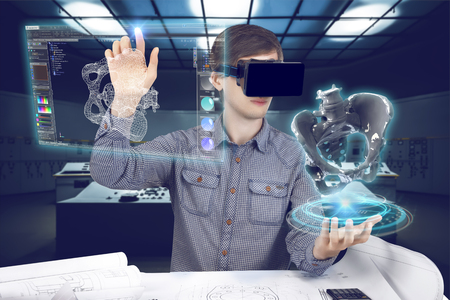 Foto de Futuristic medical scientist workplace. Male / man wearing shirt and vr glasses holding holographic prosthesis of coxal and touches virtual screen making medical analysis on futuristic plant background with control panels. - Imagen libre de derechos